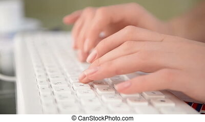 Woman typing on white keyboard