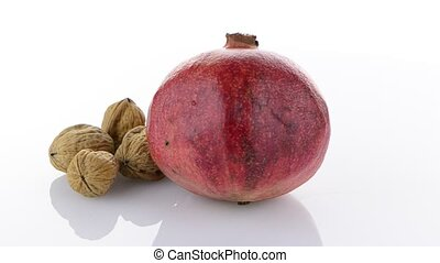 Ripe pomegranate fruit and nuts isolated on white...