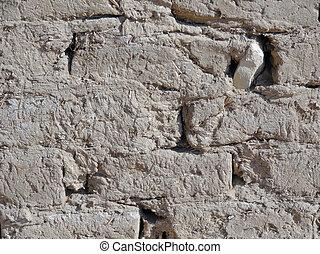 adobe wall - detail of a sunny illuminated adobe wall seen...