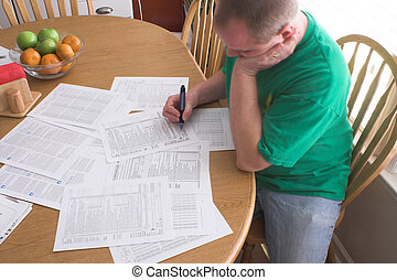 Man Doing Taxes - A man doing his taxes in the kitchen.