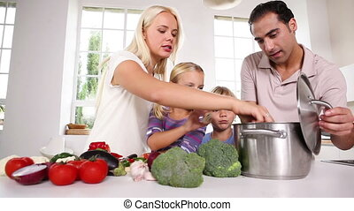 Posing family putting vegetables in a pot together