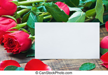 red roses and white card with a place for a congratulatory text on a wooden table