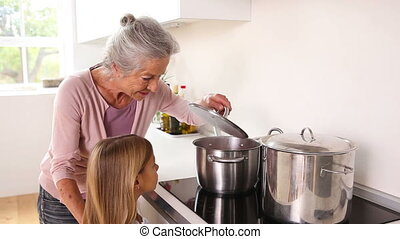 Girl happily cooking with her grandmother in kitchen