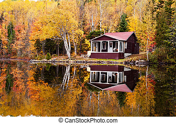 Reflections of a autumn forest and a house in a lake -...