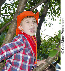 Happy Childhood - A happy boy in a tree yelling to friends