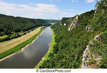 Elbe River flows through beautiful region with rocks and...