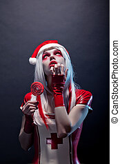 Santa Claus helper woman in red latex outfit holding...