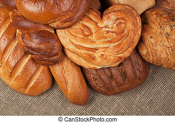 variety of fresh bread over sacking background