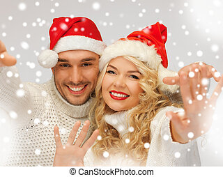 family couple in sweaters and santa's hats - picture of...