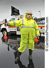 State worker directs traffic from flood area - Worker in...