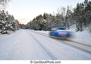 Blue car on winter road - Blue car in blurred motion on...
