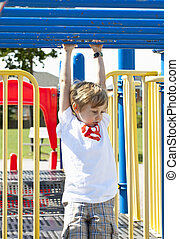 elementary boy on monkey bars - Elementary boy hanging on...