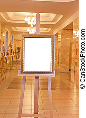 wooden picture frame on easel in art gallery