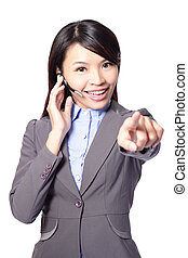 business woman with headset and smiling pointing to you...