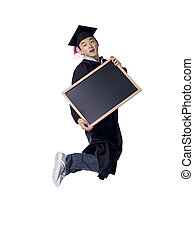 male graduate jumping while holding a black board - Portrait...
