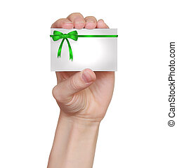 Hand holding card with green gift bows and ribbon isolated on white background