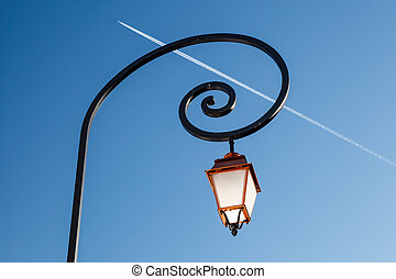 Shining Backlit Streetlamp and Airplane Trail in Background,...