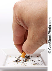Bad habit - Hand stubbing out a cigarette on white ashtray...