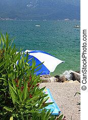 Beach umbrella - A beach umbrella on a beach at lake garda,...