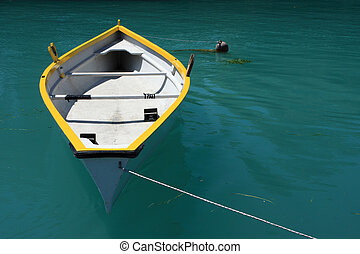 empty rowboat - A yellow and white rowing boat on deep green...