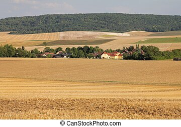 Little countryside village in northern France with harvested...