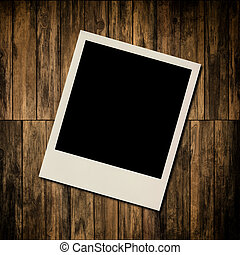 Blank instant photo frame on old wooden background