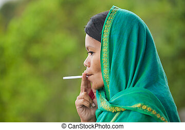 Smoking woman - South-east asian woman with head dress...