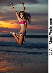 Jumping woman - Young beautiful asian woman with long black...