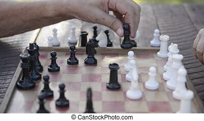 Senior men playing chess game - Active retired persons, old...
