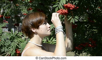 Young woman looking at rowan tree