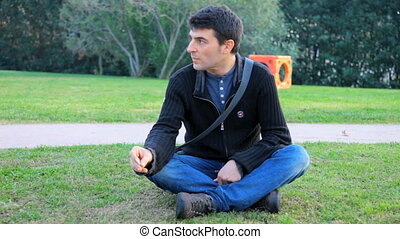 man smoking in park relaxed - Happy man smoking with no...