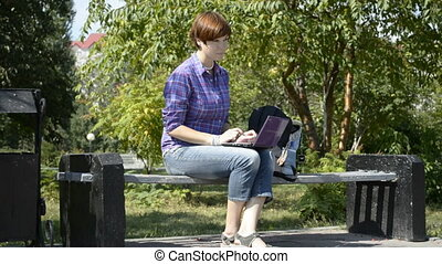 A student uses a laptop on a park