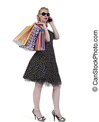 Portrait of a young woman with shopping bags talking on...