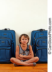 Unhappy traveller - A young girl sits in front of suitcases,...