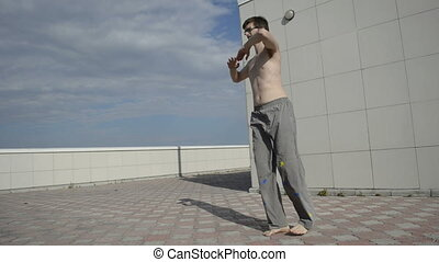Man practices yoga on the roof Flapping feet, hands at...