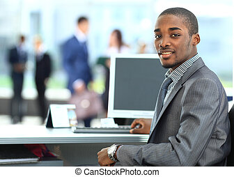 Portrait of a happy African American entrepreneur displaying...
