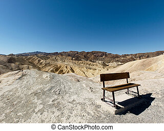 Empty bench - A wooden bench with the the Death Valley...