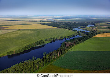 aerial view above the green fields and river