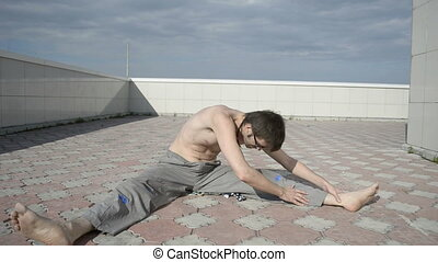 Man practices yoga on the roof Stretching the back, legs...
