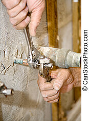 Plumber Tightens Valve - Closeup of plumbers hands using...