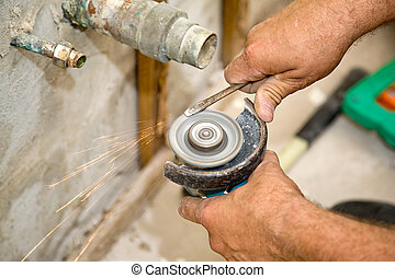 Plumbing - Sparks Fly - Plumber using a hand held grinder to...