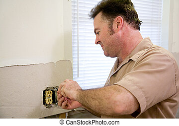 Electrician Repairs Outlet - Electrician repairing an...
