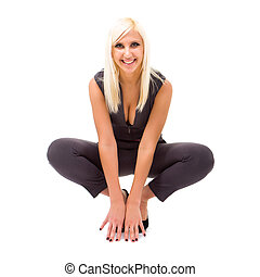 smiling woman wearing a fashionable jumpsuit sitting on an...
