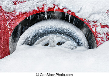 Car tire covered with snow winter blizzard