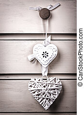 Two vintage hearts - A wicker and a tin heart hanging from...