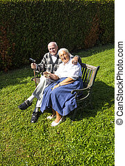 elderly couple sitting in their garden and enjoy life