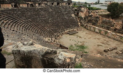 Man sitting on the stone chair in ancient amphitheater Myra