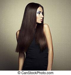 Portrait of beautiful brunette woman in black dress