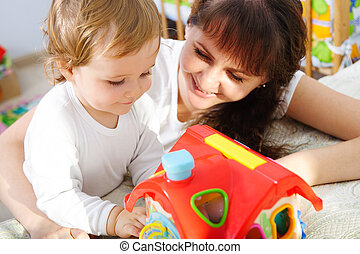 Young mother playing with her little son with toys at home