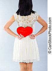 Brunette girl in white dress with red Valentine heart Rear...